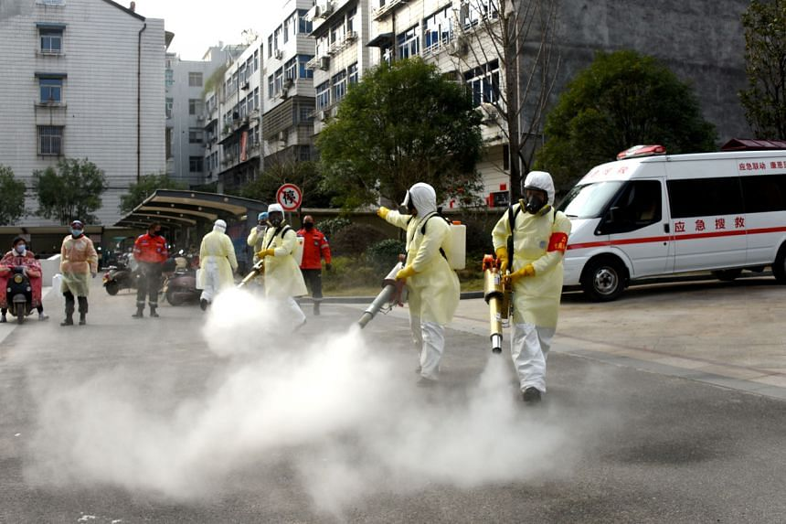 Volunteers in protective suits disinfect a residential compound in Taizhou, Zhejiang province, China, on Jan 30, 2020.