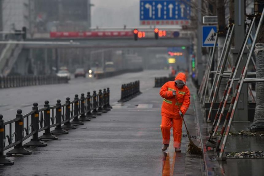A worker wearing a protective face mask sweeps a street in Wuhan on Jan 25, 2020. The Singapore Red Cross is making a public appeal for funds to aid the communities in China affected by the coronavirus outbreak that originated in Wuhan.