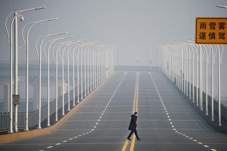 A man who arrived from Hubei Province in China crossing the Jiujiang Yangtze River Bridge near a checkpoint in Jiujiang, Jiangxi Province, on Jan 31, 2020.