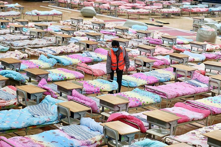 A worker setting up beds yesterday at the Hongshan Stadium to help convert the sports facility into a makeshift hospital following the coronavirus outbreak in Wuhan, Hubei province.