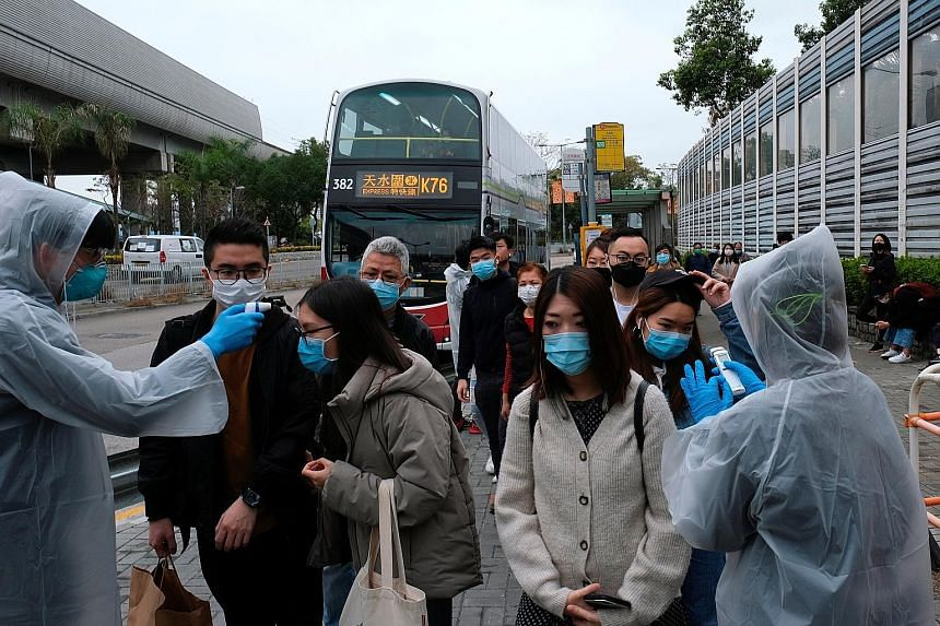 Volunteers checking people's temperatures at a bus stop in Tin Shui Wai, a border town in Hong Kong, yesterday. The city now has 17 confirmed infections, with four suspected to be local transmissions.