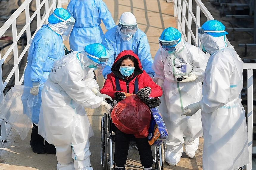 Medical staff transferring a patient to the newly completed Huoshenshan Hospital in Wuhan, Hubei province, yesterday. Two temporary hospitals have been built in under two weeks to ease the bed shortage.