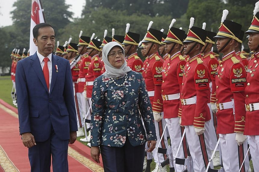 Indonesia's Vice-President Ma'ruf Amin meeting President Halimah at the Shangri-la Hotel in Jakarta yesterday. PHOTO: LIANHE ZAOBAO Singapore President Halimah Yacob, accompanied by Indonesian President Joko Widodo, inspecting a guard of honour at th