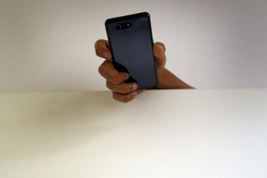 Posed photo of a hand holding a mobile phone over a partition. No video of the girl was found on the device later.