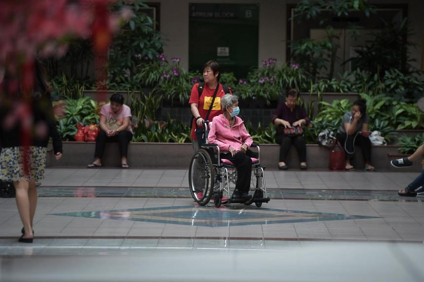 An elderly lady in a wheelchair wearing a mask at Tan Tock Seng Hospital, on Feb 4, 2020.