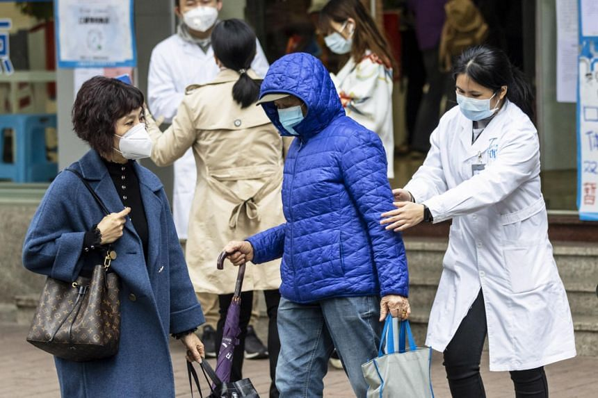 Pharmacy employees give information to people in front of a local pharmacy about results of the government's lottery for protection masks for coronavirus in Guangzhou, Guangdong Province, China, on Feb 2, 2020.