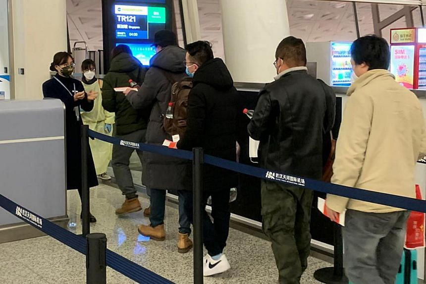 Singaporeans queueing up at Wuhan Tianhe International Airport to board the Scoot flight that would take them home.