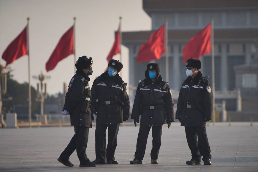 Police officers wearing masks are seen at the Tiananmen Square, as the country is hit by an epidemic of the new coronavirus, in Beijing, China, on Jan 30, 2020.