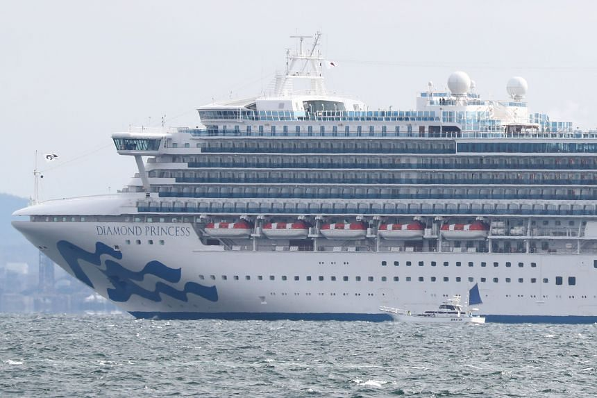 A small boat is pictured next to the Diamond Princess cruise ship with over 3,000 people as it sits anchored in quarantine off the port of Yokohama, on Feb 4, 2020, a day after it arrived with passengers feeling ill.