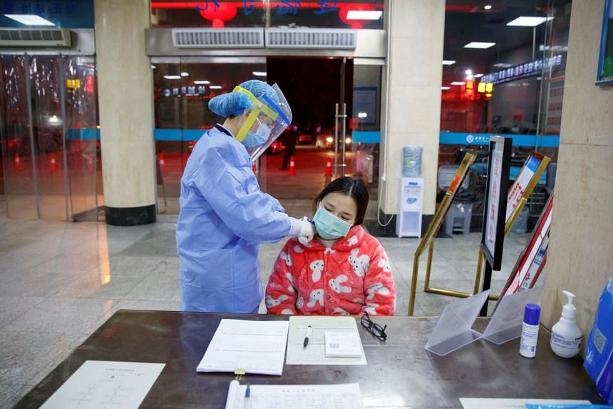A nurse taking the temperature of a woman in the reception area of the First People's Hospital in Yueyang, China, on Jan 28, 2020. Currently, in testing for the coronavirus, a nurse uses a swab to collect secretions from the patient's throat for test