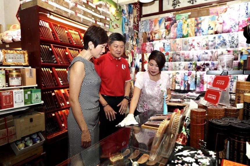 Manpower Minister Josephine Teo (left) and National Trades Union Congress secretary-general Ng Chee Meng (centre) visited Chinatown Street Market to ensure that standards are being met to keep shops and streets clean and workers protected from infect