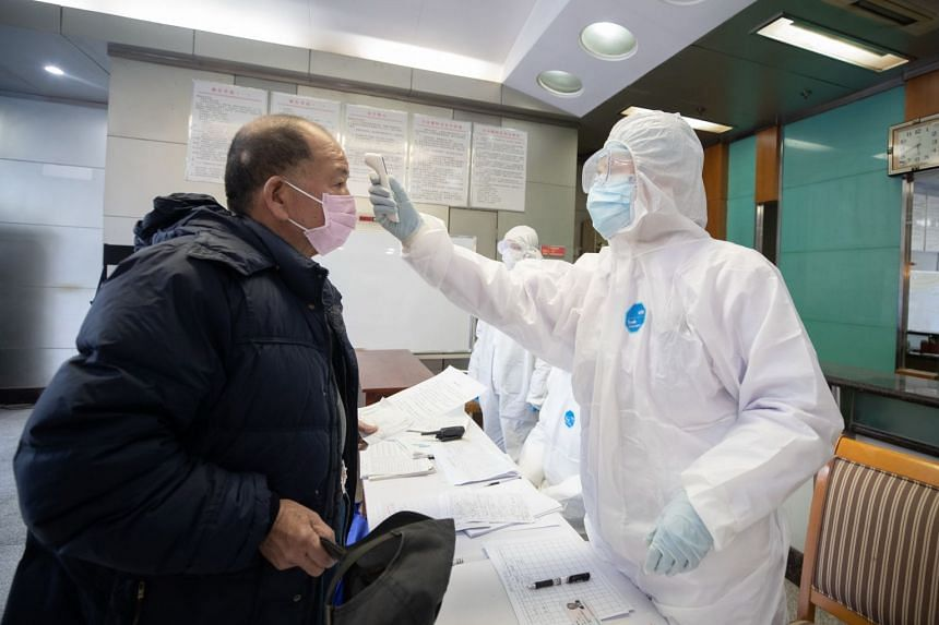 A medical staff member checks the temperature of a patient quarantined at a hotel in Wuhan city.