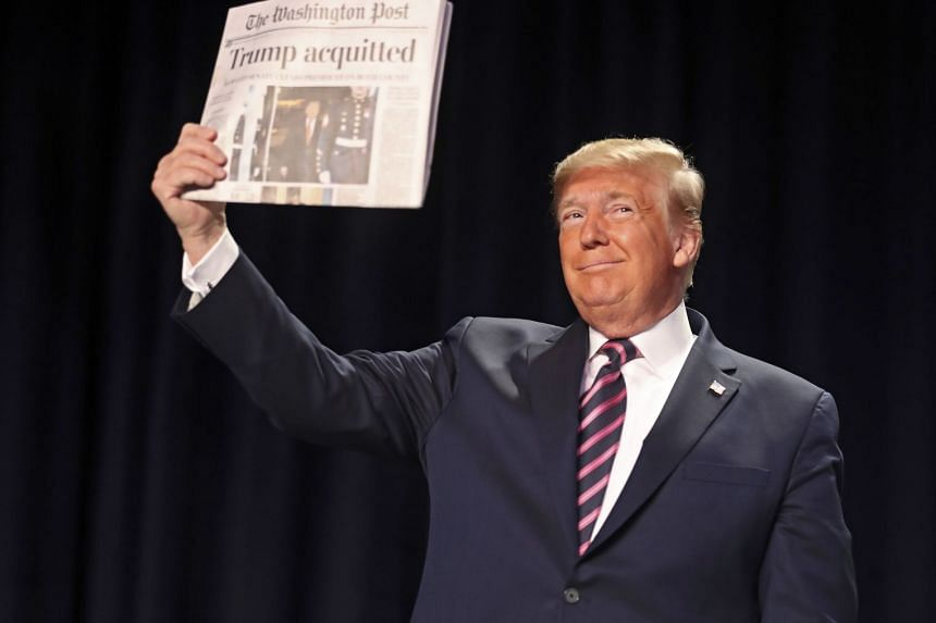 Trump holds a copy of the Washington Post newspaper featuring his Impeachment acquittal, as he arrives at the prayer breakfast.