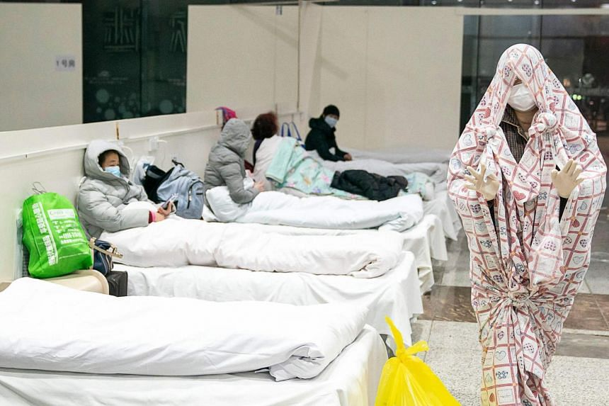 A photo taken on Feb 5, 2020, shows a patient (right) covered with a bed sheet at an exhibition centre converted into a hospital in Wuhan.