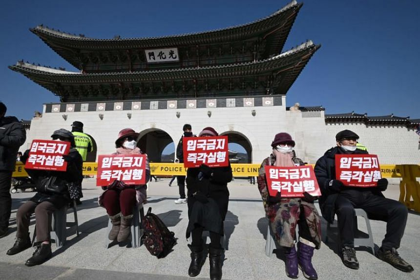 """Protesters hold signs reading """"Ban entry immediately"""" during a protest calling on the South Korean government to enforce an entry ban on Chinese visitors against the spread of the new coronavirus, in front of Gyeongbokgung palace in Seoul, on Feb 3,"""