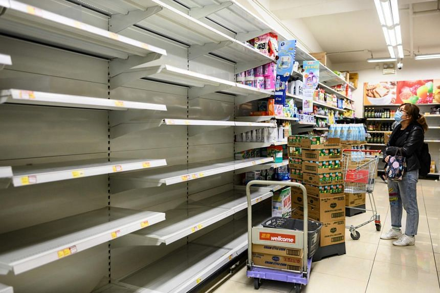A woman wearing a face mask looking at empty supermarket shelves, which used to stack paper towels, in Hong Kong, on Feb 5, 2020.