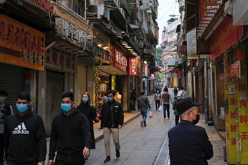 People wear masks as they walk near Ruins of St. Paul's in Macau on Feb 5, 2020.