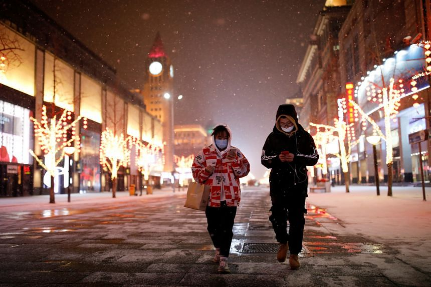 People wearing face masks walk along a street in Beijing on Feb 5, 2020.