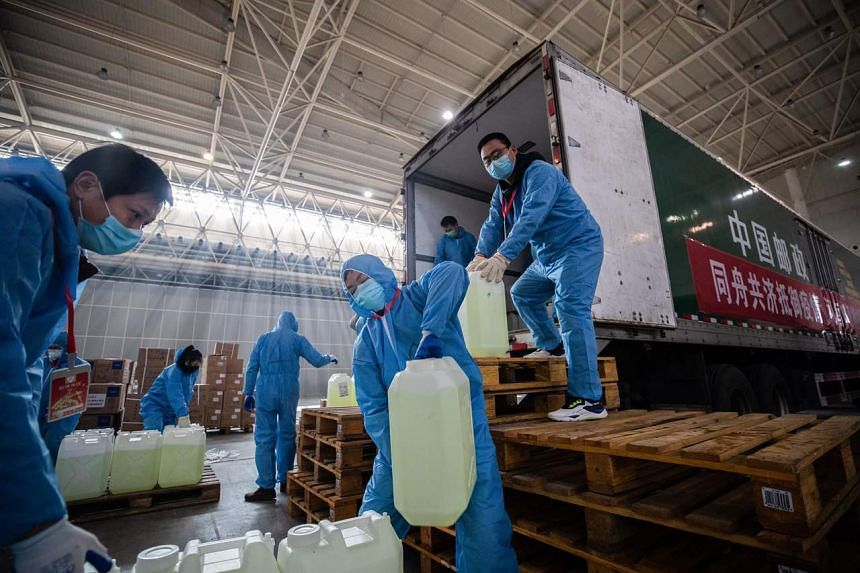 Staff members and and volunteers wearing protective face masks offloading medical supplies at a warehouse in Wuhan, China, on Feb 4, 2020.