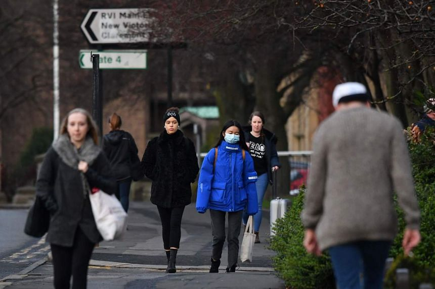 In a photo taken on Jan 31, 2020, a pedestrian wearing a protective face mask walks outside the Royal Victoria Infirmary in Newcastle-upon-Tyne, in north-east England.