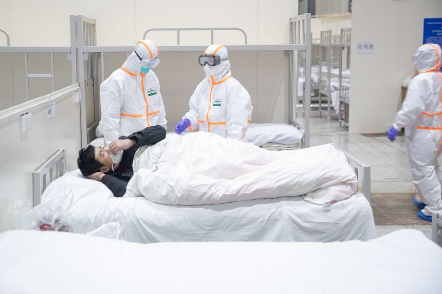 Medical staff attending to a patient infected by the coronavirus at a makeshift hospital at Wuhan International Convention and Exhibition Centre, on Feb 5, 2020.