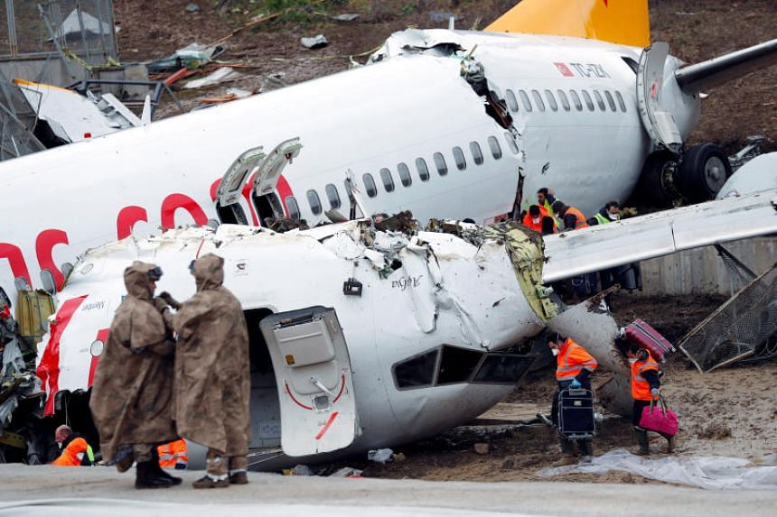 People work at the Pegasus Airlines Boeing 737-86J plane wreckage, after it overran the runway during landing and crashed, at Istanbul's Sabiha Gokcen airport, Turkey, on Feb 6, 2020.