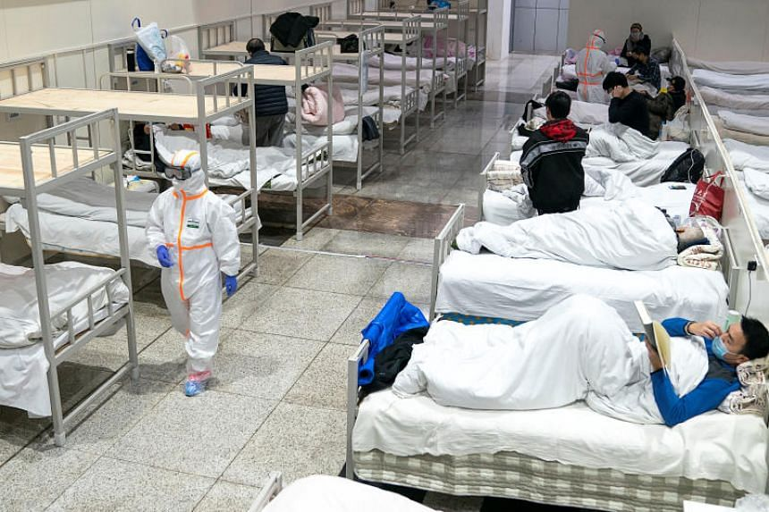 Medical workers in protective suits attending to patients at the Wuhan International Conference and Exhibition Centre, which has been converted into a makeshift hospital to receive patients infected by the novel coronavirus, in Wuhan, China, on Feb 5