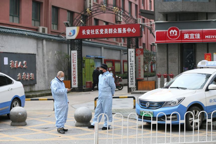 Taxi drivers in protective suits are waiting in front of a residential area in Wuhan, China, on Jan 28, 2020.