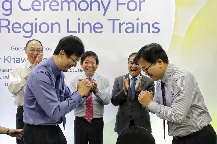 Mr Ngien Hoon Ping (in blue), LTA chief executive, and Mr Choi Dong-hyun, vice-president and chief operating officer of railway business division at Hyundai Rotem, congratulating each other after the signing ceremony. Looking on are (from left) LTA c