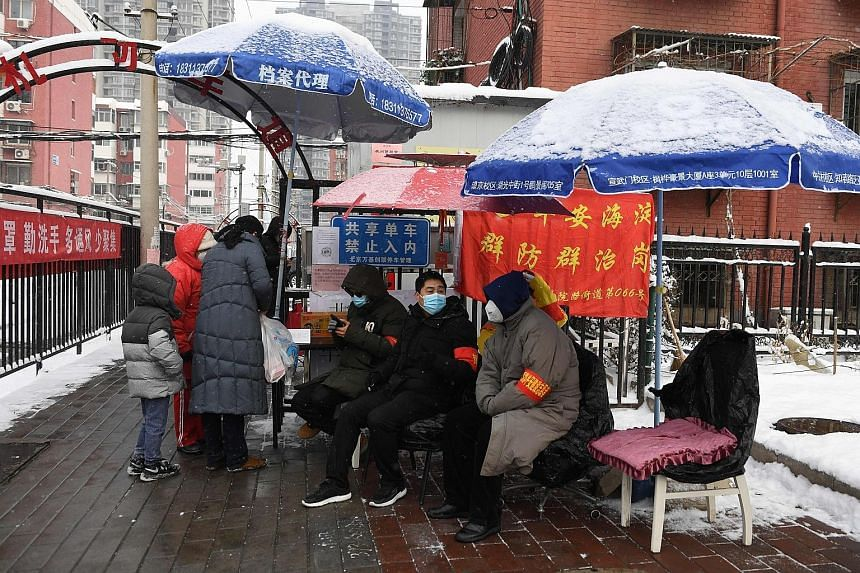 Residents monitoring the entrance to a residential compound in Beijing yesterday. Most Chinese are living in fear and staying home, but there is no widespread chaos or mass exodus - a sign that the Communist Party's credibility is pretty much intact.
