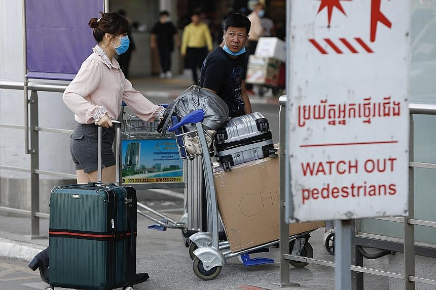 Travellers donning masks at Phnom Penh International Airport in the Cambodian capital on Wednesday. China's allies like Cambodia and Pakistan have said they will not extricate their citizens from China's Hubei province in what is seen as a diplomatic