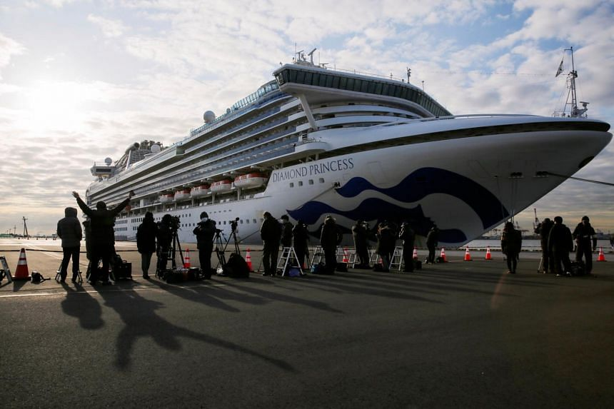Journalists are seen next to the cruise ship Diamond Princess as it is anchored at Daikoku Pier Cruise Terminal in Yokohama, south of Tokyo, Japan, on Feb 7, 2020.