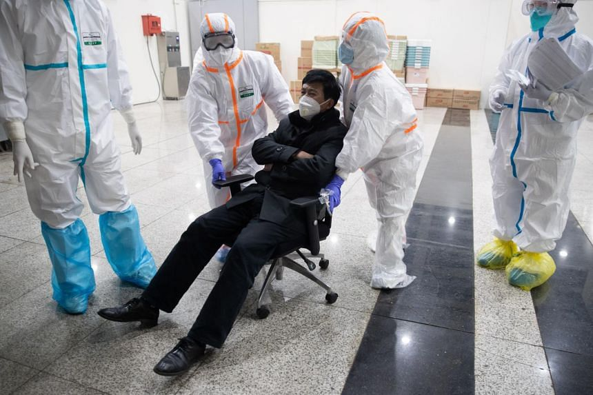 A patient infected by the coronavirus is received at a makeshift hospital at Wuhan International Convention and Exhibition Centre in Wuhan on Feb 5, 2020.
