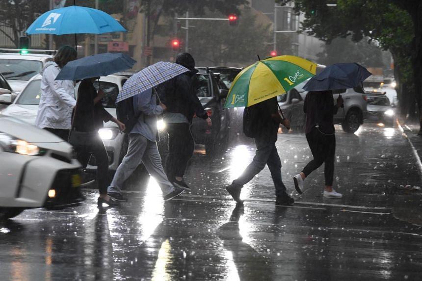 Pedestrians hold umbrellas during wet weather in Sydney, Australia, on Feb 7, 2020.