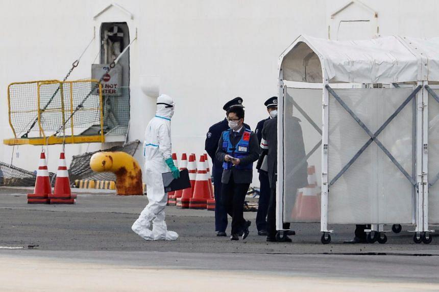 Men wearing protective gear are seen near the cruise ship Diamond Princess at Daikoku Pier Cruise Terminal in Yokohama, Japan, on Feb 7, 2020.