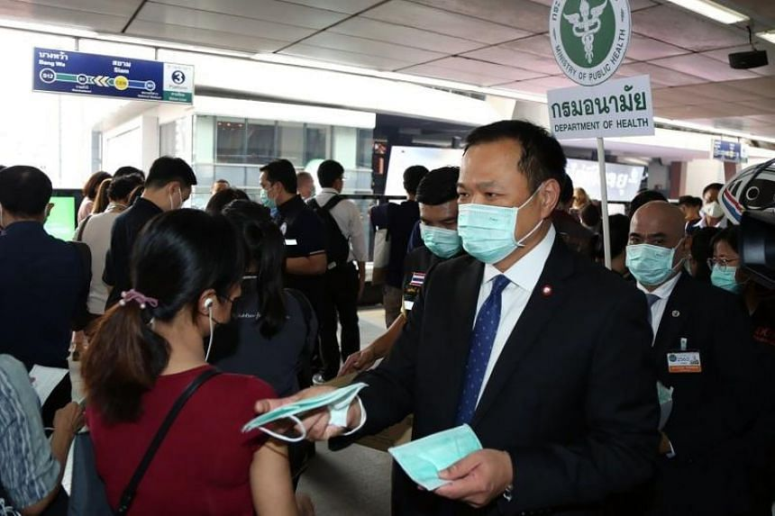 Thai Health Minister Anutin Charnvirakul (right) handing out face masks to members of the public at a BTS Skytrain station in Bangkok on Feb 6, 2020.