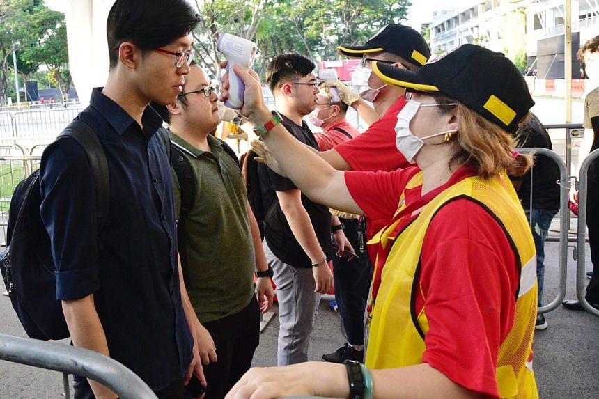 Visitors having their temperature checked before entering the Chingay Parade at the F1 Pit Building on Jan 31, 2020. Singapore moved its disease outbreak response up a level to orange on Feb 7 as the coronavirus spread further within the country.
