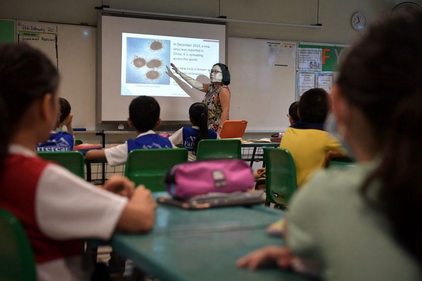 A teacher showing a slide about the coronavirus to Primary 4 pupils during their Character and Citizenship Education (CCE) class at Farrer Park Primary School, on Jan on 7, 2020.