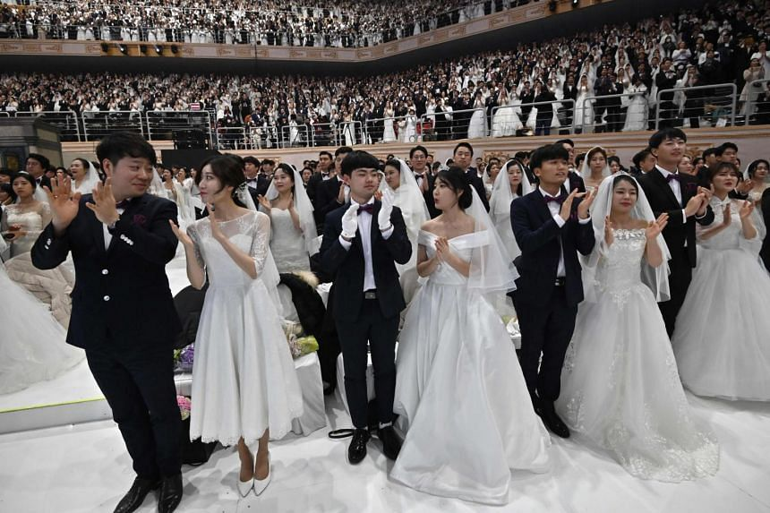Couples attend a mass wedding ceremony organised by the Unification Church at Cheongshim Peace World Centre in Gapyeong on Feb 7, 2020.
