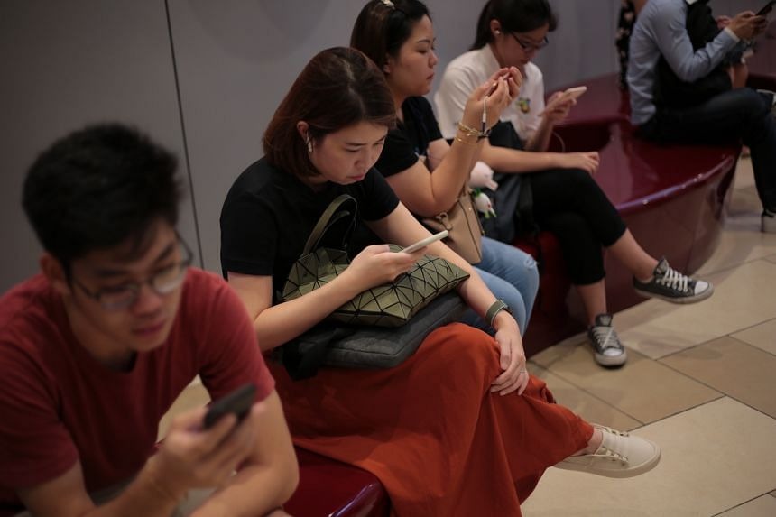 People using their mobile phones at Bedok Mall on Nov 1, 2019.