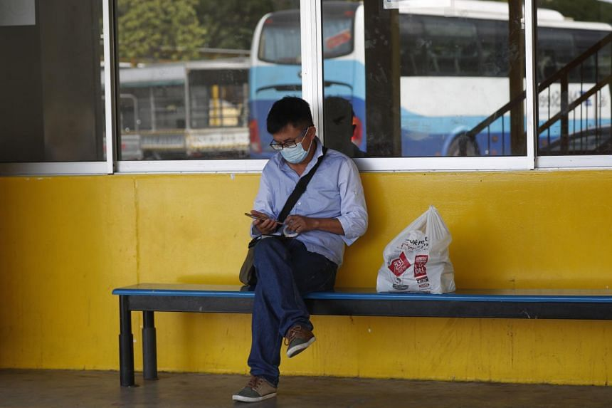 A man wearing a surgical mask uses a mobile phone at the Tuas View dormitory in Singapore, on Feb 6, 2020.