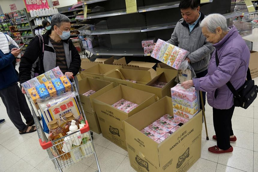 Empty shelves are seen in a supermarket as customers in Hong Kong on Feb 7, 2020, pick up facial tissues following the coronavirus outbreak.