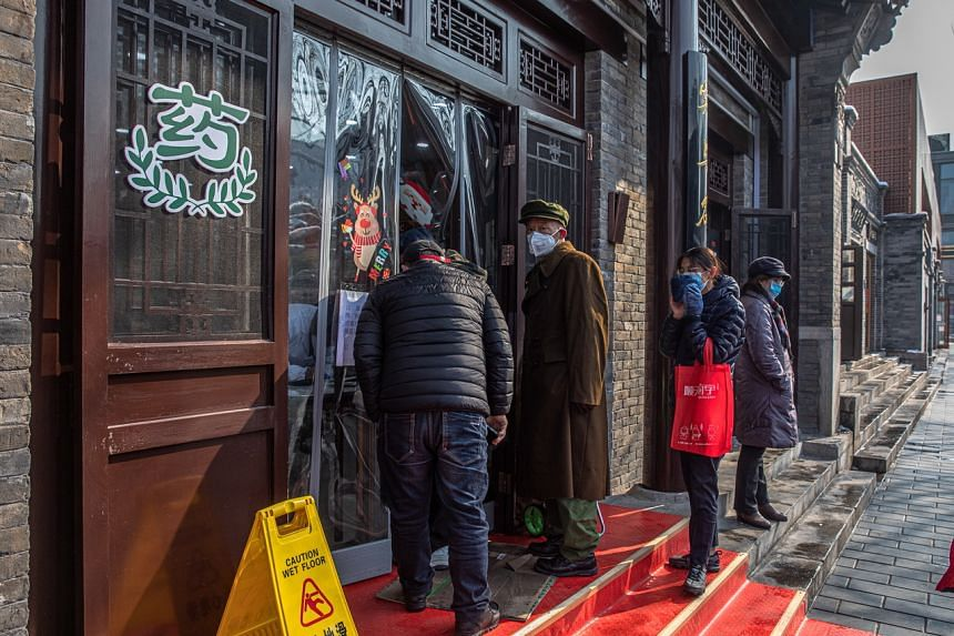 People wearing protective face masks queue outside a pharmacy at Hutong neighborhood, in Beijing, on Feb 7, 2020.