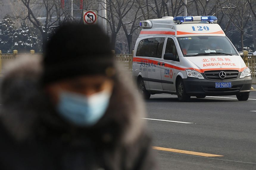 A man wears a face mask as an ambulance drives by in Beijing on Feb 7, 2020.