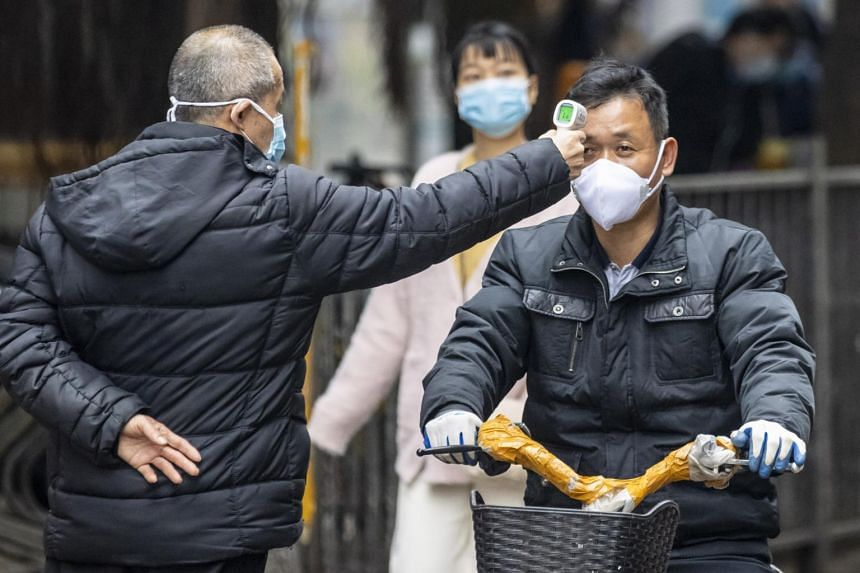 A security guard checks a man's temperature at a seafood market in Guangzhou, on Feb 6, 2020.
