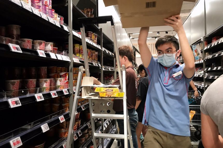 An employee working to restock shelves at FairPrice Xtra at VivoCity on Feb 8, 2020.