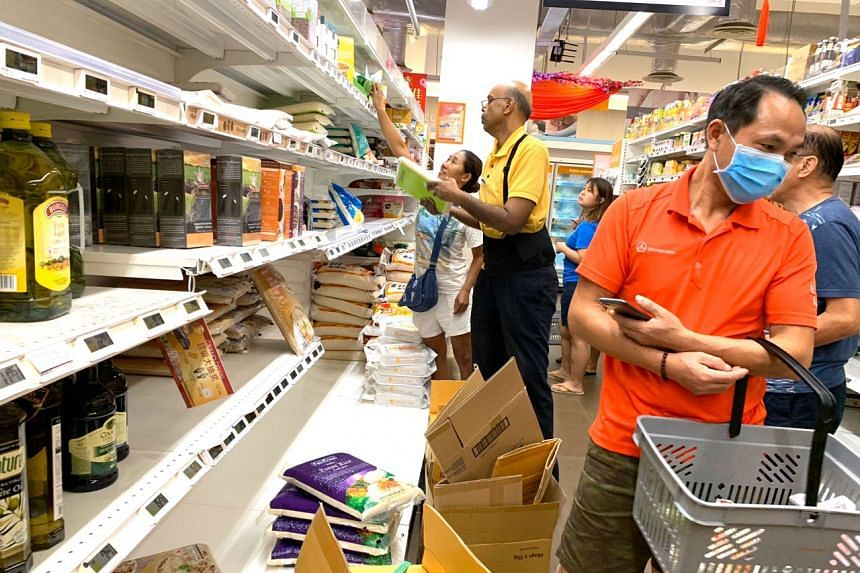 An employee replenishing bags of rice onto the shelves at the FairPrice Finest outlet at myVillage in Serangoon Garden on Feb 8, 2020.