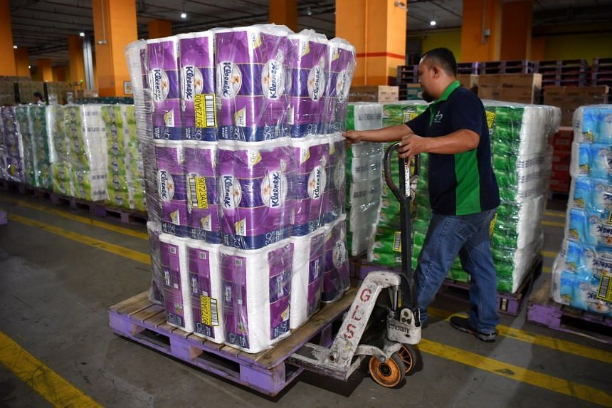 A worker moves paper products at NTUC Fairprice's Benoi Distribution Centre on Feb 8, 2020.