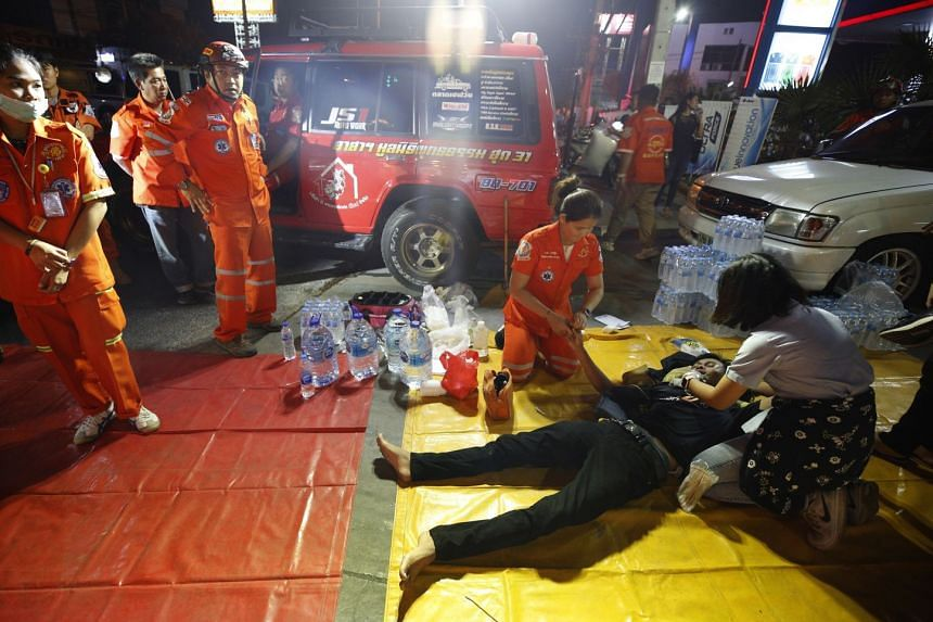 Thai rescue workers help an injured victim.