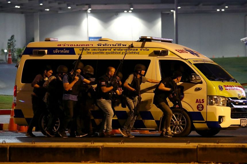 Thai security forces take cover behind an ambulance as they hunt down the shooter.